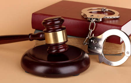 Gavel, handcuffs and book on law on beige background Stock Photo - 17052324