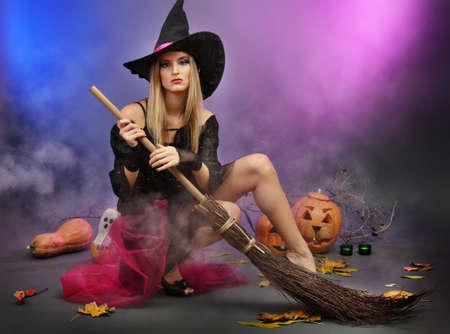 bruja sexy: Bruja de Halloween con una escoba sobre fondo de color Foto de archivo
