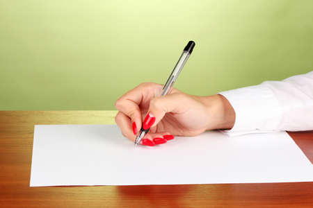 Hands writing on  paper on green background Stock Photo - 17052223