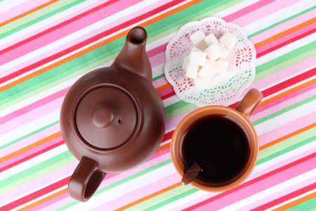 Top View Of Cup Of Tea And Teapot On Colorful Tablecloths Photo