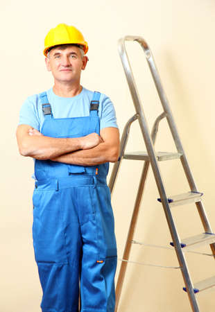 Builder in helmet near  stairs on wall background photo