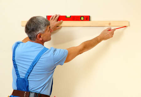 repairmen: Builder measuring wall in room close-up Stock Photo