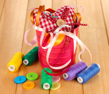 Color bucket with multicolor ribbons and thread on wooden background Stock Photo - 17052117
