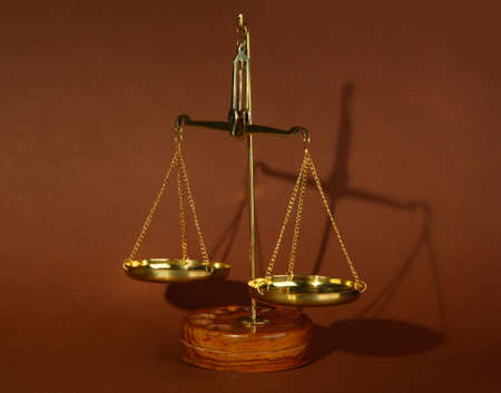 Gold scales of justice on brown background photo