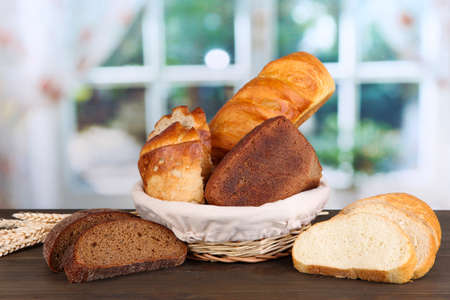 Fresh bread in basket on wooden table on window background Stock Photo - 17052436
