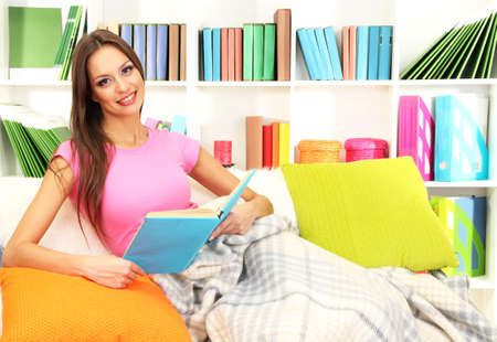 Portrait of female reading book while lying on couch photo