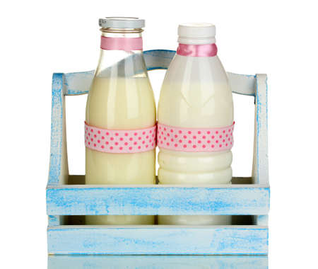 Milk in bottles in wooden box isolated on white photo