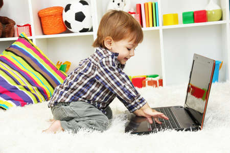cute little boy and notebook in room Stock Photo - 17052469