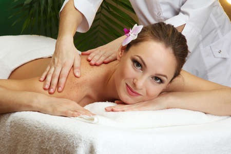 beautiful young woman in spa salon getting massage, on green background Stock Photo - 17282480
