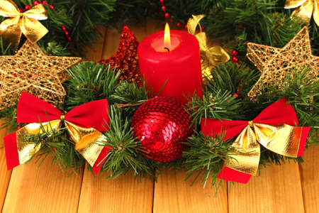 Christmas composition  with candle and decorations in red and gold colors on wooden background Stock Photo - 17053294