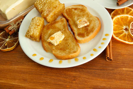 White bread toast with honey and cup of coffee on wooden table photo