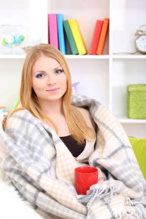 Attractive young woman sitting on sofa, holding cup with hot drink, on home interior background Stock Photo - 17281546
