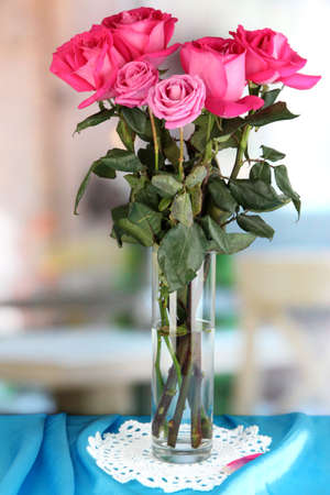 Beautiful pink roses in vase on blue fabric table on room background Stock Photo - 17053111