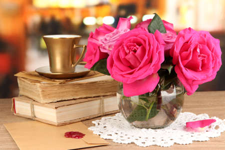 Beautiful pink roses in vase on wooden table on room background photo