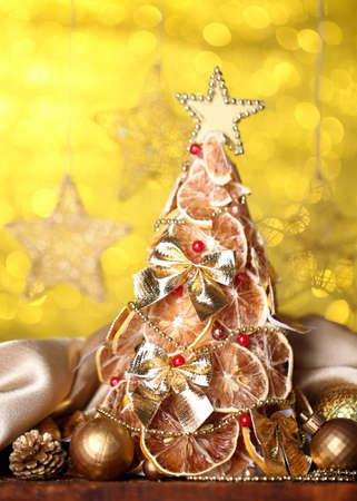 beautiful christmas tree of dry lemons with decor, on  yellow background photo