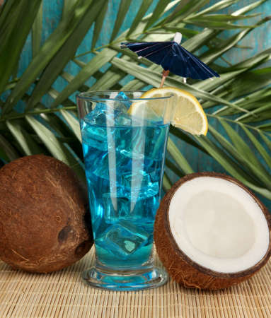 Blue Lagoon cocktail with coconut on tropical background photo