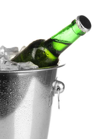 Beer bottle in ice bucket isolated on white photo