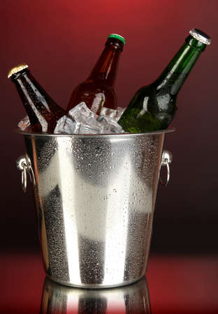 Beer bottles in ice bucket on darck red background photo
