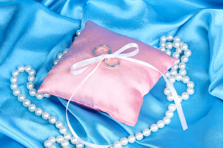 Wedding rings on satin pillow on blue cloth background photo