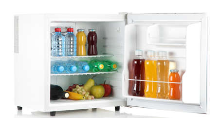 frigo: mini-r�frig�rateur rempli de bouteilles de jus de fruits, soda et fruits isol� sur blanc Banque d'images