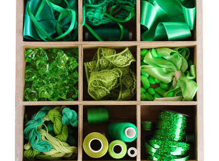 Green thread and material for handicrafts in box isolated on white photo