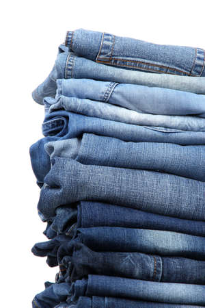 Many jeans stacked in a pile isolated on white photo
