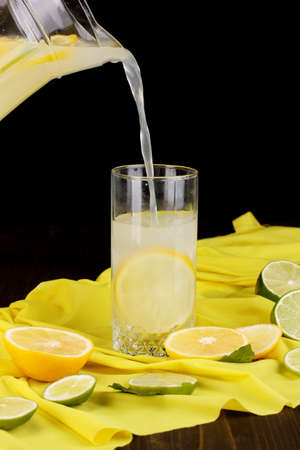 Citrus lemonade in glass and pitcher of citrus around on yellow fabric on wooden table close-up Stock Photo - 17052701