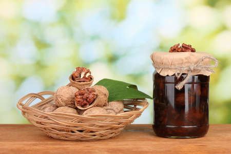 jam-jar of walnuts on wooden table and a basket with walnuts on green background Stock Photo - 17053185