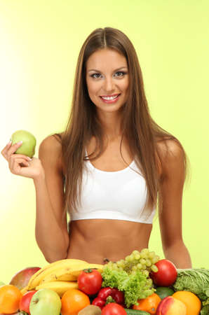 beautiful young woman with fruits and vegetables, on green background photo