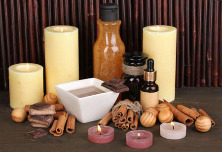 Beautiful chocolate spa setting on wooden table bamboo background with reflection photo