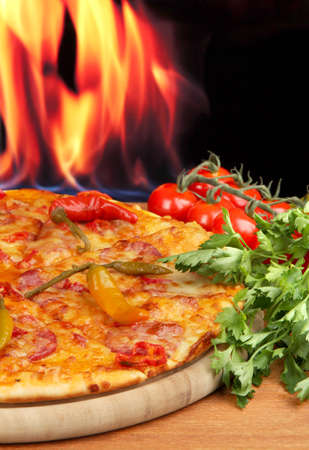 Tasty pepperoni pizza with vegetables on wooden board on flame background Stock Photo - 17053241