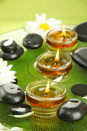 spa stones with flowers and candles in water on plate photo