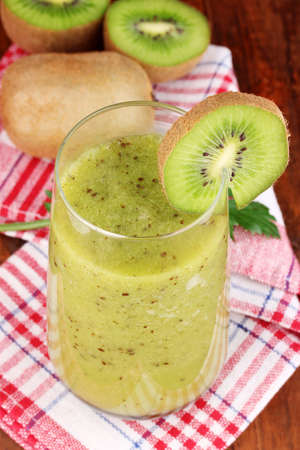 Glass of fresh kiwi juice on wooden table photo