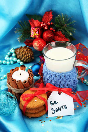 Cookies for Santa: Conceptual image of ginger cookies, milk and christmas decoration on blue background photo