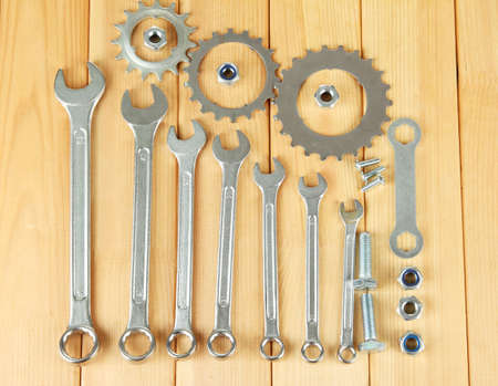 Machine gear, metal cogwheels, nuts and bolts on wooden background photo