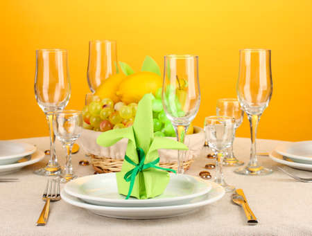 Table setting in green and yellow tones on color  background photo