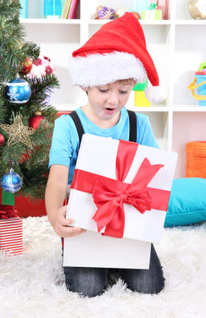 Little boy open his gifts near Christmas tree photo