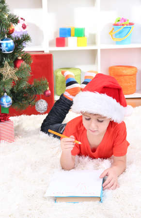 Little boy in Santa hat writes letter to Santa Claus Stock Photo - 17282583