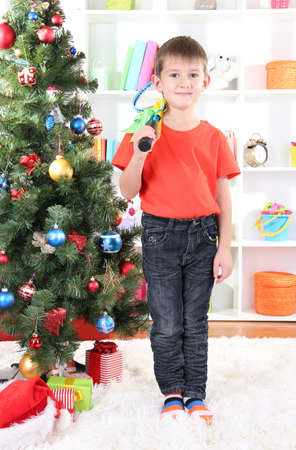Little boy stands near Christmas tree with badminton rackets photo