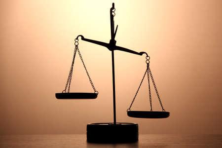 balance scale: Escamas de oro de la justicia sobre fondo marr�n Foto de archivo