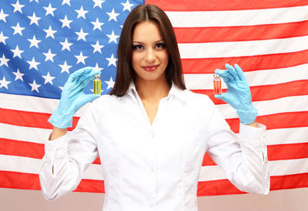 Portrait of female doctor or scientist showing and analyzing liquid in flask over American Flag background Stock Photo - 17281939