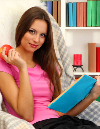 Portrait of female eating apple and reading book at home Stock Photo - 17281920