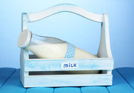 Milk in bottle in wooden box on blue wooden table on blue background photo