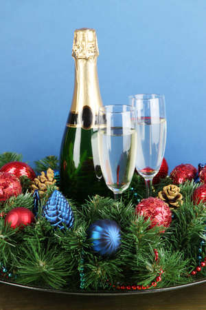 Beautiful Christmas wreath in composition with champagne on blue background photo