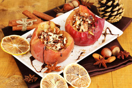 Baked apples on plate on wooden table photo