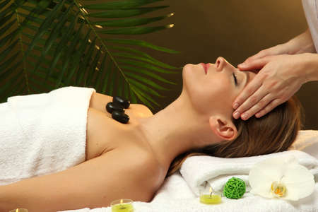 Portrait of beautiful woman with spa stones taking head massage photo