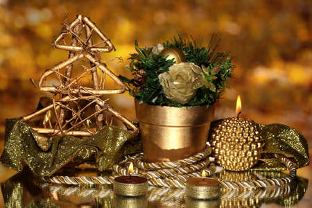 Christmas composition  with candles and decorations in gold color on bright background photo