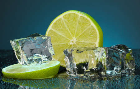 Ice cubes with lime on darck blue background photo