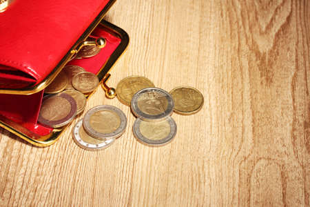 economise: female red wallet with coins on wooden background Stock Photo