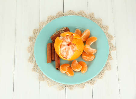 Tasty mandarines on color plate on light background photo